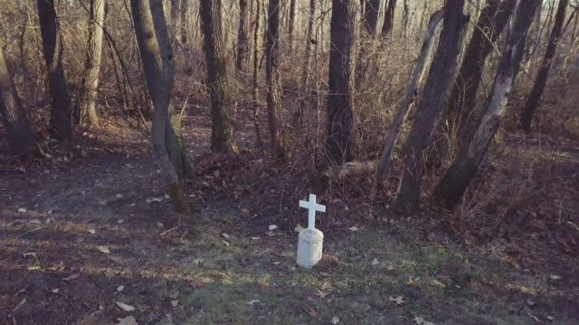 orbital shot of a stone cross at the spanish flu epidemic mass grave site - buried stock videos & royalty-free footage