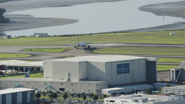 orbital shot of an airplane taxiing at the auckland airport - 飛行機格納庫点の映像素材/bロール