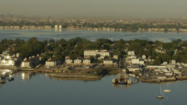 Orbital shot of City Island homes with boats anchored in the harbor