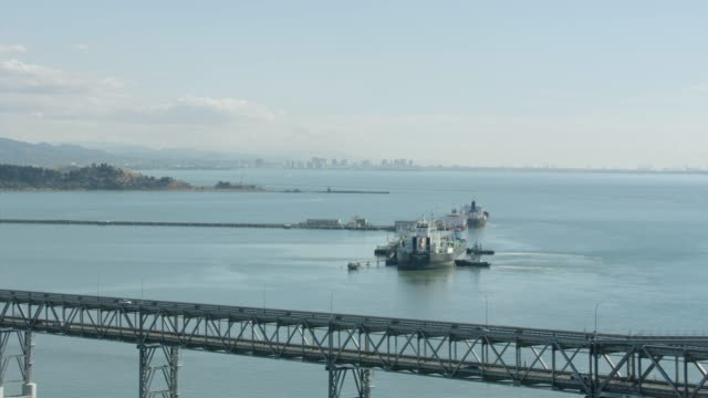 orbital shot of docking tanker ships in the chevron long wharf with the richmond-san rafael bridge in the foreground - san francisco bay stock videos & royalty-free footage