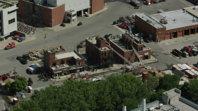 orbital shot of firefighter trainees practicing at a building at the fire department of the city of new york training center - fire department of the city of new york stock videos and b-roll footage