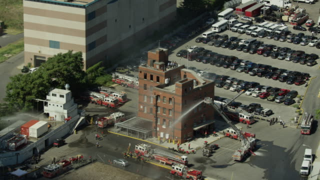 orbital shot of firefighter trainees practicing on the roof of a smoking building and a simulated container ship at the fire department of the city of new york training center - fire department of the city of new york stock videos and b-roll footage
