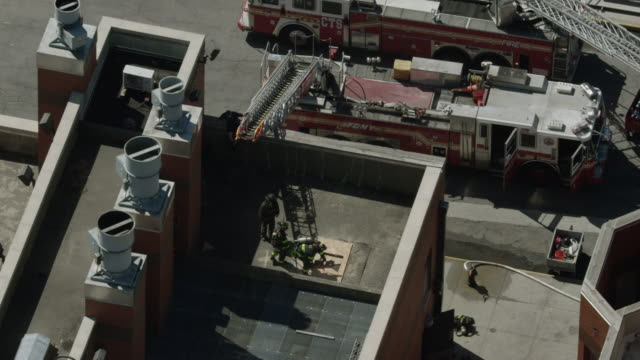 orbital shot of firefighter trainees sawing through a rooftop at the fire department of the city of new york training center - fire department of the city of new york stock videos and b-roll footage