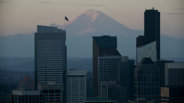 stockvideo's en b-roll-footage met orbital shot of high-rise buildings at downtown seattle with mount rainier in the background at sunrise - seattle