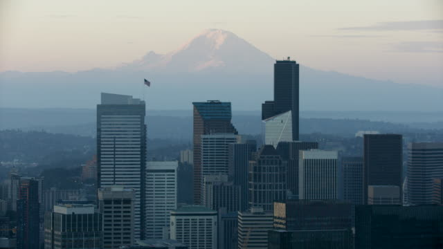 orbital shot of high-rise buildings at downtown seattle with mount rainier in the background at sunrise - seattle stock videos & royalty-free footage