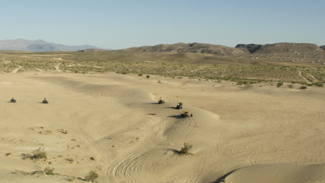 orbital shot of people driving off-road motor vehicles in the nellis sand dunes - dune buggy stock videos and b-roll footage