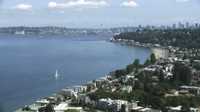 orbital shot of the alki beach park with downtown seattle in the background - seattle stock-videos und b-roll-filmmaterial