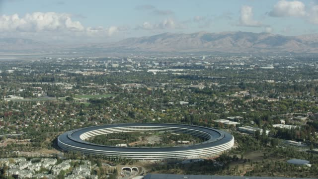 orbital shot of the apple park with a mountain range in the background - silicon valley stock videos & royalty-free footage