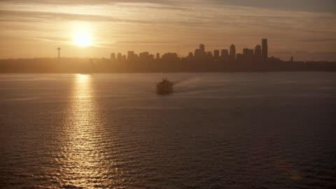 orbital shot of the bainbridge island ferry at sunrise - elliott bay stock videos & royalty-free footage