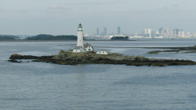 orbital shot of the boston light with downtown boston in the background - region new england stock-videos und b-roll-filmmaterial