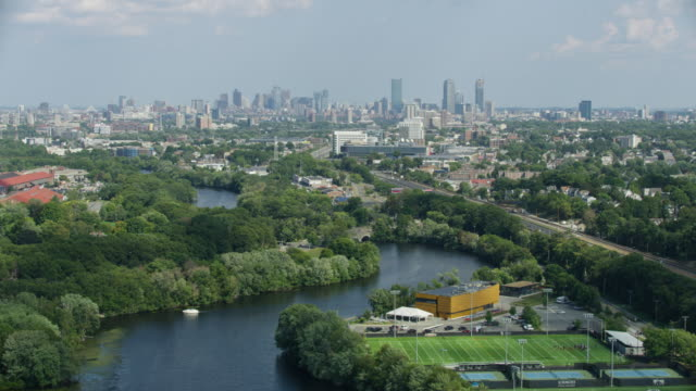 orbital shot of the daly field athletics complex with boston downtown in the background - チャールズ川点の映像素材/bロール