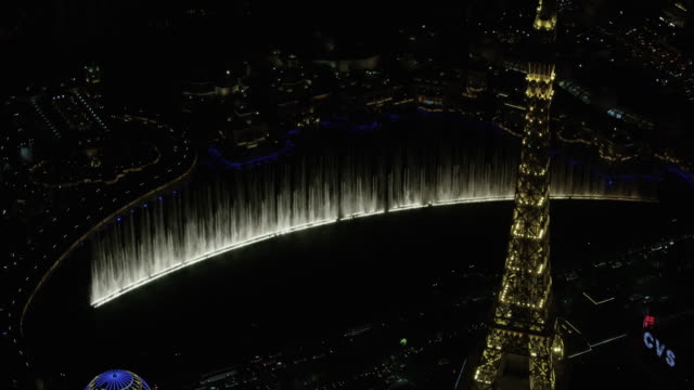 orbital shot of the fountains of bellagio with the eiffel tower replica in the foreground in las vegas at night - replica eiffel tower stock videos & royalty-free footage