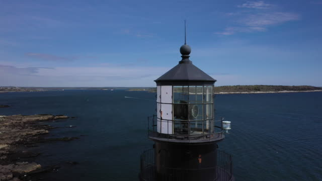 orbital shot of the portland head light in casco bay - pull out camera movement stock videos & royalty-free footage