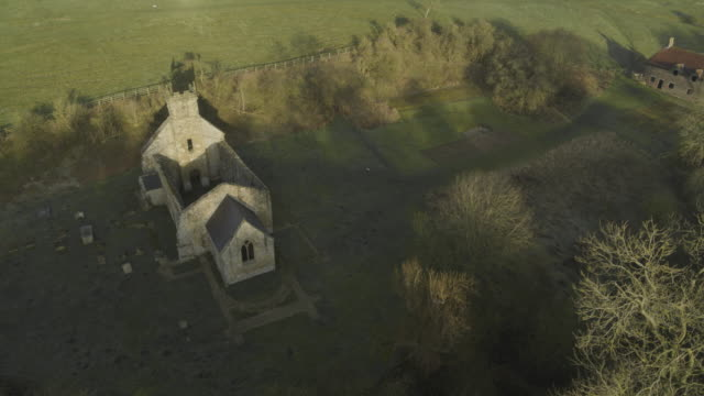 orbital shot of the ruined st martins church and the graveyard of wharram percy - boundary stock videos & royalty-free footage