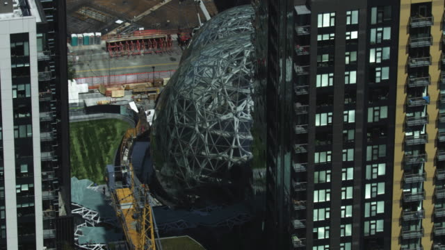 orbital shot of the spheres with high-rise buildings in the foreground - シアトル点の映像素材/bロール