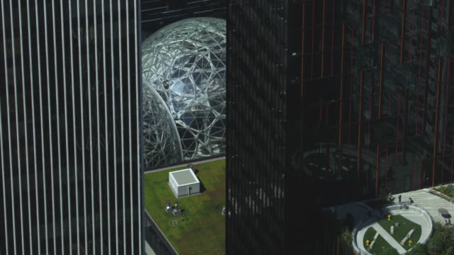 orbital shot of the spheres with high-rise buildings in the foreground - seattle video stock e b–roll