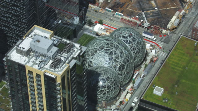 orbital shot of the spheres with high-rise buildings in the foreground - seattle stock-videos und b-roll-filmmaterial