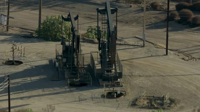 stockvideo's en b-roll-footage met orbital shot of working pumpjacks in the inglewood oil field - ruw materiaal