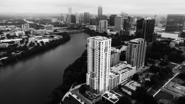 vídeos de stock e filmes b-roll de orbiting around austin texas black and white drone views above cityscape - town