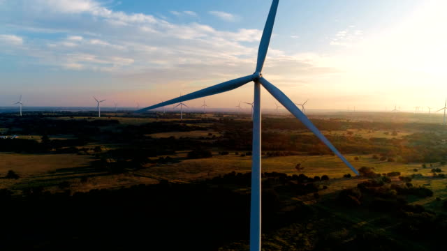 Orbiting around Wind Turbine during morning golden hour sunrise
