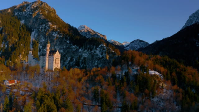 as orbiting the neuschwanstein castle in schongau at sunset, germany - wop productions stock-videos und b-roll-filmmaterial