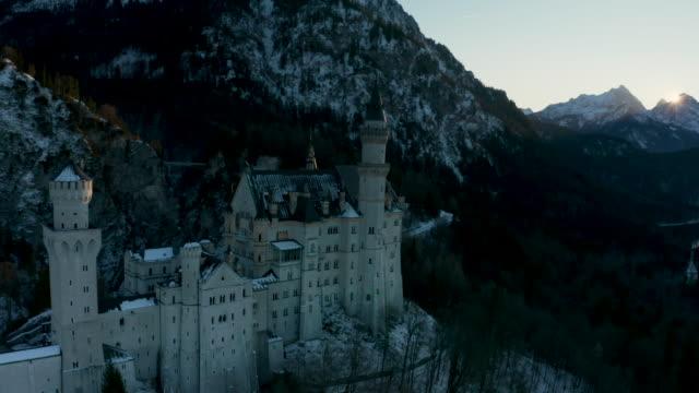 vidéos et rushes de as orbiting the neuschwanstein castle in schongau at sunset, germany - allemagne