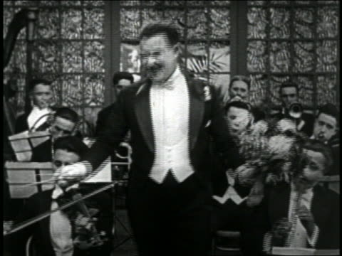 vidéos et rushes de b/w 1919 orchestra conductor smelling bouquet of flowers while conducting + sneezing / short - 1910 1919