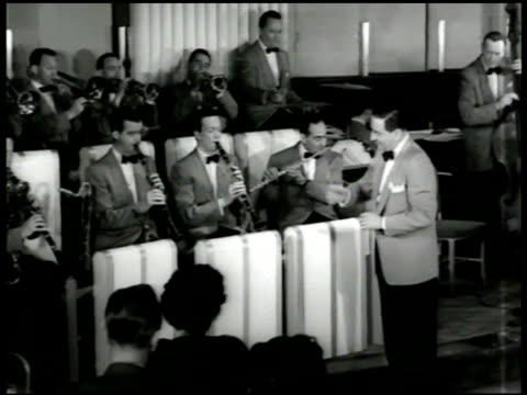 Orchestra leader Guy Lombardo conducting band playing 'Everywhere You Go' MS Lombardo conducting w/ baton VS Band saxophone players bass fiddle...