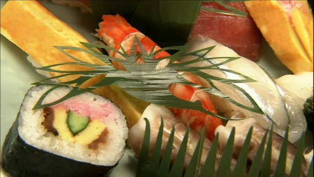 orchid leaves cut into crane and turtle patterns provide an unusual garnish. - nigiri stock videos and b-roll footage