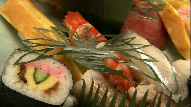orchid leaves cut into crane and turtle patterns provide unusual garnishes. - nigiri stock videos and b-roll footage