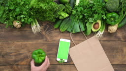 Order food online smartphone with blank screen and paper bag on wooden table fresh green vegetables