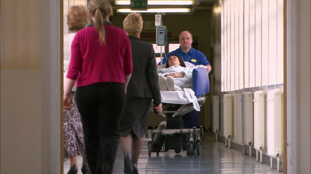 orderly wheeling patient down corridor - krankenhaus rollbett stock-videos und b-roll-filmmaterial