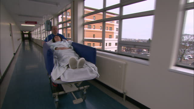 orderly wheeling patient down corridor - trolley stock videos and b-roll footage