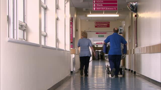 vídeos de stock, filmes e b-roll de orderly wheeling patient down corridor - vista traseira