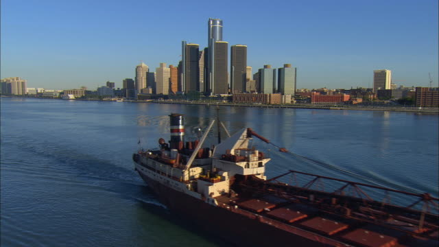 WS Ore carrier ship on Detroit River passing Renaissance Center and downtown cityscape near Grand River Avenue / Detroit, Michigan, USA