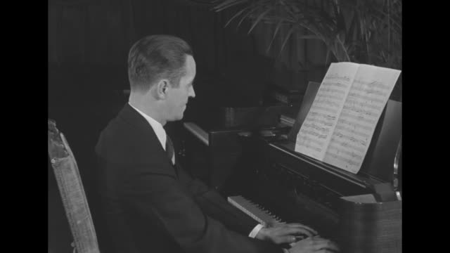vídeos de stock, filmes e b-roll de vo organ music from offcamera duet partner as organist joins in then stops to adjust regulator knobs on organ as vo duet partner continues to play he... - chord