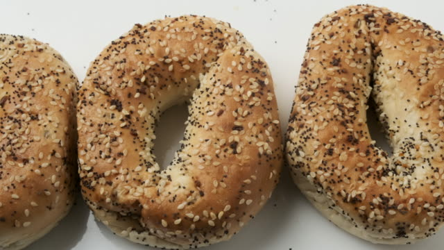 organic everything bagels from above on white background - bagel stock videos & royalty-free footage