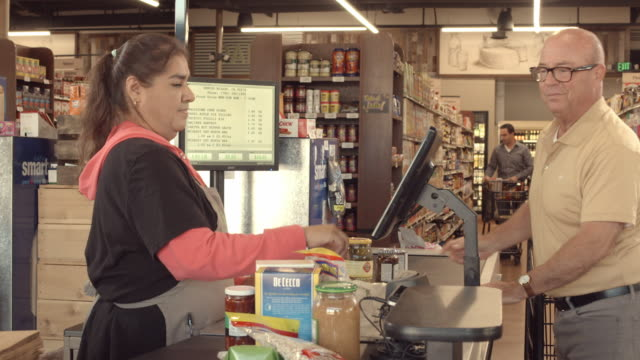 ds organic food store checkout counter as mature adult man places grocery items on conveyor belt while checker punches each item into computer screen - assistant stock videos and b-roll footage