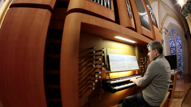 ms tu organist looking in music book and playing organ   / saarburg, rhineland-palatinate, germany - パイプオルガン点の映像素材/bロール