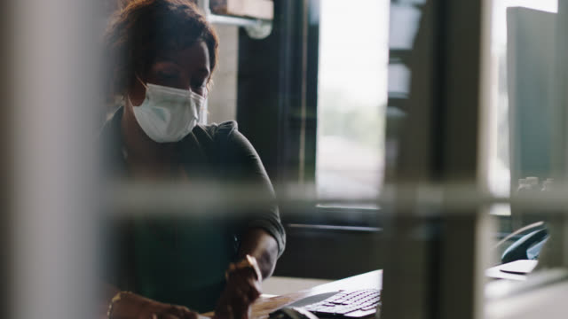 organized businesswoman wearing face mask sits at computer desk in office, looks at clipboard, writes on sticky note - clipboard stock videos & royalty-free footage