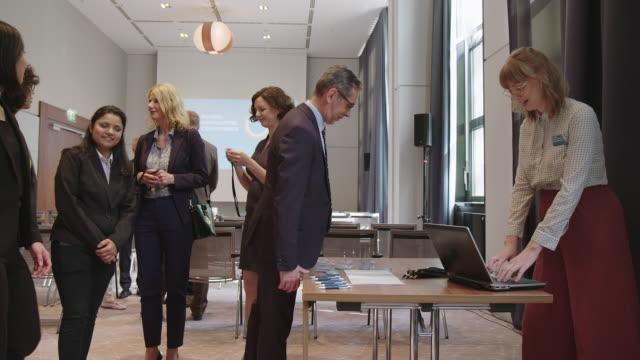 vídeos de stock e filmes b-roll de organizer distributing id cards to colleagues - conferência de negócios