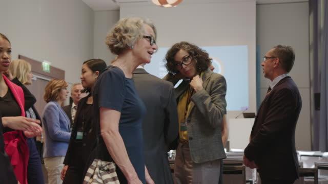 vídeos y material grabado en eventos de stock de organizador dando cordones a ejecutivos en el hotel - congreso de negocios