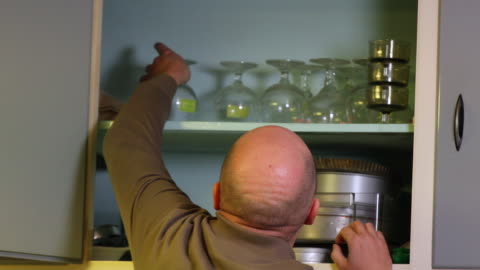 stockvideo's en b-roll-footage met organizing and cleaning kitchen cabinet. - genderblend