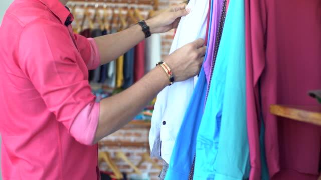 vídeos de stock, filmes e b-roll de organizando a loja de roupas - óculos