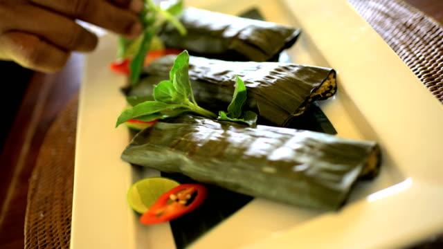 vídeos y material grabado en eventos de stock de oriental banana leaves wrapping vegetables with basa gede - cultura indonesia