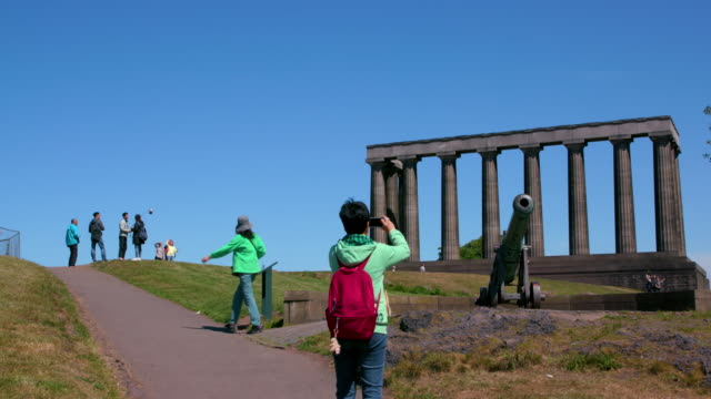 oriental tourists at the portugese cannon & national monument of scotland, calton hill, edinburgh, scotland - calton hill national monument stock videos and b-roll footage