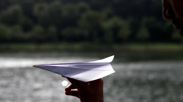 vídeos y material grabado en eventos de stock de avión de origami en la mano y el bokeh de agua de la piscina - avión de papel