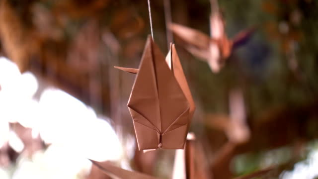 vídeos de stock e filmes b-roll de origami of bird paper craft hanging closeup, unique paper toy turning around in wind for decoration, creativity - stock video - arte e artesanato arte visual