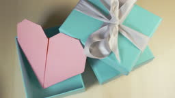 Origami pink heart inside a turquoise gift box