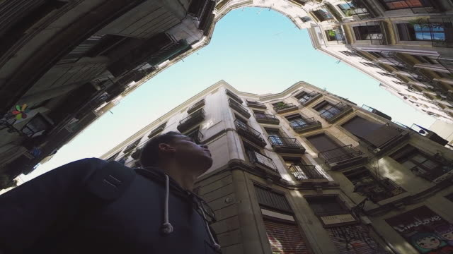vídeos de stock e filmes b-roll de original below view recorded with wide angle lens in a beautiful round street with nice vanishing point and narrow street in the barcelona city with tourist traveler visiting it and contemplating. - apartamento
